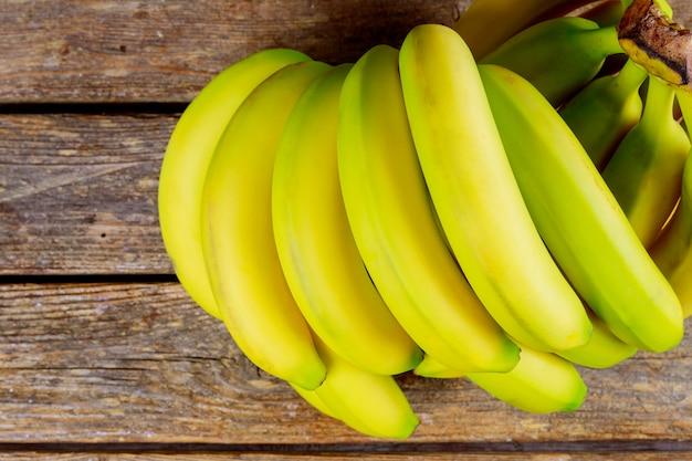 木製のテーブルに熟したバナナの束。