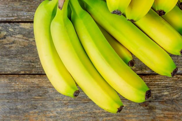 新鮮なバナナの木製の背景に束