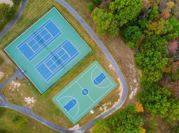 Открытый теннисный корт и баскетбольная площадка в парке с высоты осенью