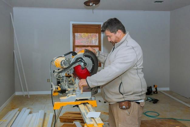 労働者は、のこぎりで木製のベースボードをカットします