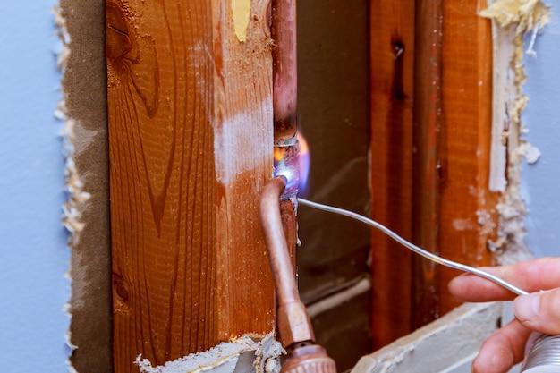 銅パイプガスバーナーのろう付け用フラックスペーストを保持しているクローズアッププロのマスター配管工アパートのパイプラインの変更、漏れ