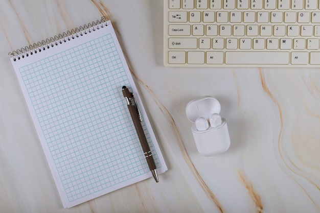 Управление на рабочем месте с клавиатуры компьютера и беспроводные наушники ноутбук, ручка работает блоггинг стол