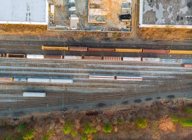 貯水池の鉄道駅のコンテナー多くのワゴンと列車の空撮。