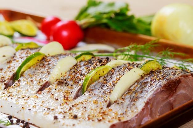 Сырое маринованное рыбное филе с луком, на противне и в духовке, готовой к приготовлению.