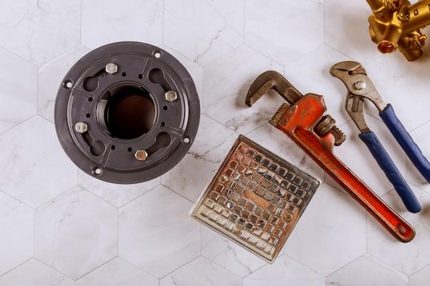 モダンなスタイルの配管器具とモンキーレンチの汚れたステンレス鋼バスシャワードレイン