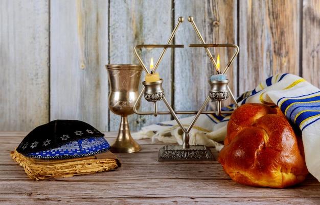 安息日ユダヤ人の休日のカラパンと木製のテーブルのカンデラ