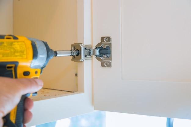 キッチン家具を組み立てるチップボード家具の取り付けヒンジ。大工のワークショップを配置します。