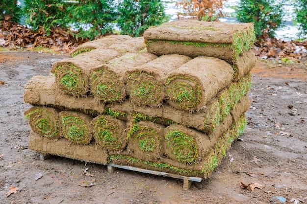 芝草のスタックは、芝生の新鮮な草の風景を飾るためにロールバックします