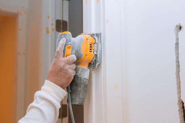 Рука рабочего шлифования и подготовки деревянной отделки молдинга для дверного обрамления интерьера дома