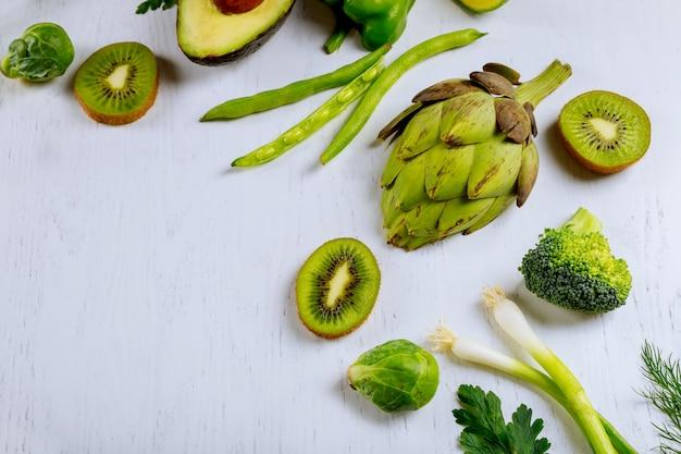 Разнообразие сырых зеленых овощей, салаты, листья салата, бок чой, кукуруза, брокколи, савойская капуста в виде рамки вокруг пустой белой разделочной доски. продовольственный фон.