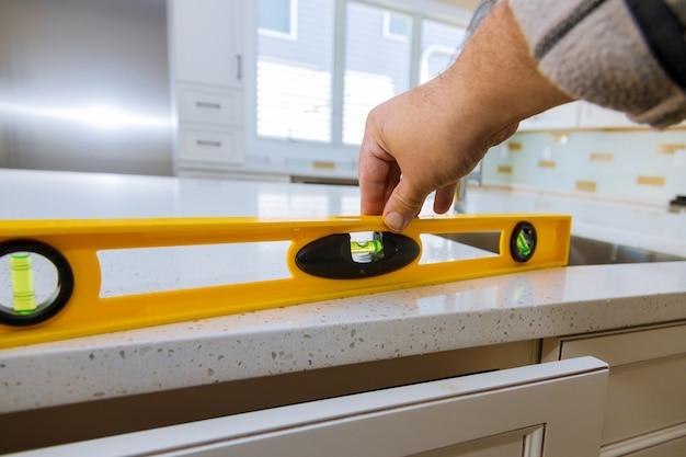 現代の家庭用キッチンキャビネットを作るカウンタートップでレベリング