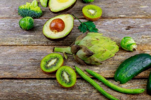木製の背景のエンドウ豆、パセリ、キュウリ、ディル、玉ねぎ、サラダの緑の野菜