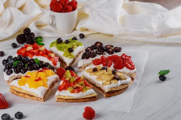 Клубнично-кремовый бисквит на домашнем летнем десерте на деревянном столе