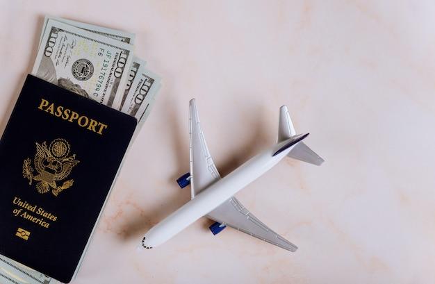 アメリカのパスポートとドル紙幣の模型飛行機、飛行機の準備のために旅行