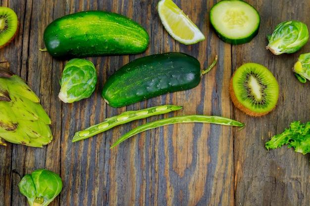 健康的な料理やサラダ作りのための新鮮な生野菜原料、センターの素朴なオリーブの木板、上面図、コピースペース。