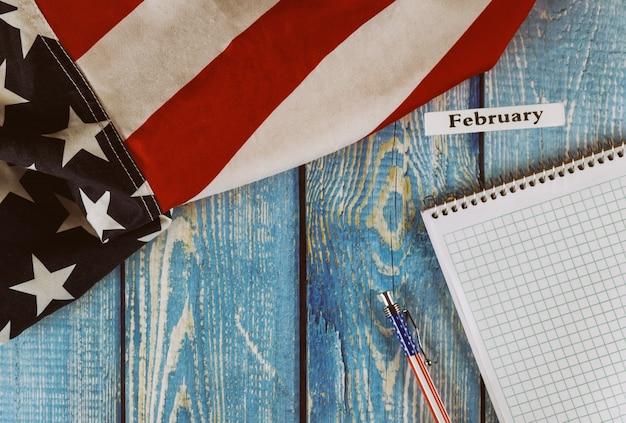 カレンダーの年の月アメリカ合衆国のメモ帳とオフィスの木製テーブルにペンで自由と民主主義の象徴の旗