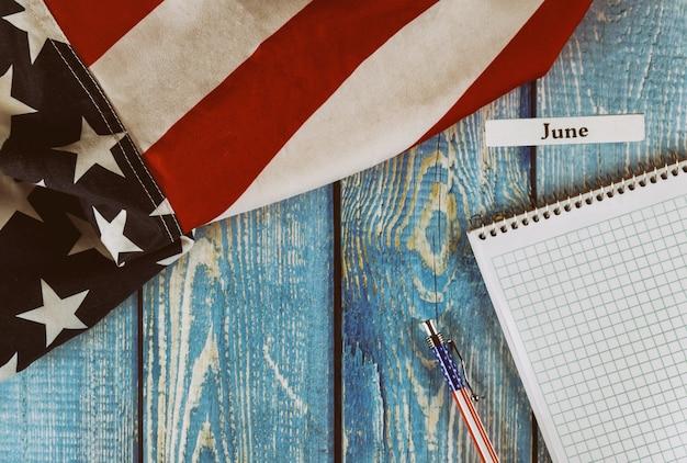 Июнь месяц календарного года флаг соединенных штатов америки с символом свободы и демократии с блокнотом и ручкой на деревянном столе в офисе