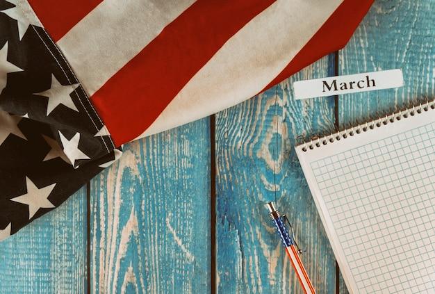 Март месяц календарного года флаг соединенных штатов америки с символом свободы и демократии с блокнотом и ручкой на деревянном столе в офисе