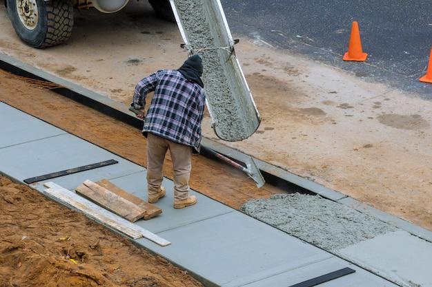 Заливка в процессе заливки бетонного цемента на недавно проложенный тротуар
