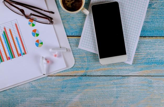 ガジェットスマートフォンとワイヤレスヘッドフォンとコーヒー、グラフと図のメガネとビジネスワークプレイス