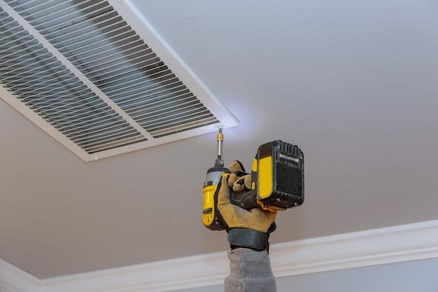 男は天井の家の冷暖房システムの通気口カバーを取り付けています
