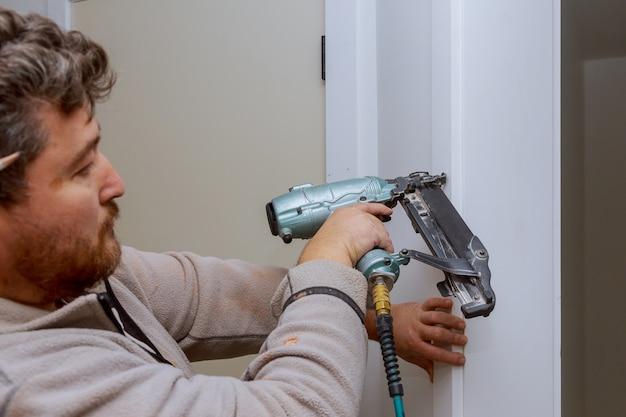 Строительный мастер с помощью пневматического гвоздевого пистолета устанавливает межкомнатную дверь квартиры