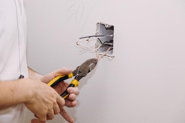 石膏壁の石膏ボード乾式壁に設置された新しい電気設備、ソケットボックス、スイッチコンセントコネクタ