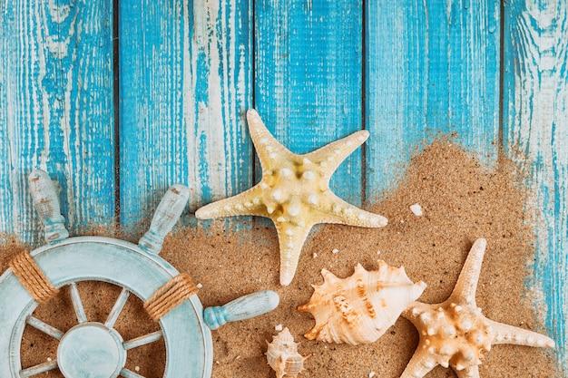 夏の旅行休暇船員のキャプテンホイールヒトデと砂の上の貝殻