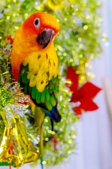 クリスマスツリーの飾りの上に座ってオウム