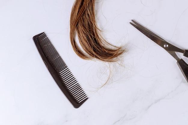 長い茶色の女性の髪、はさみ、櫛のトリミング