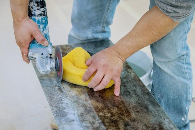 Строительный рабочий режет плитку с помощью мельницы