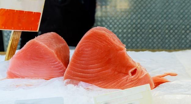 おいしい魚介類の夕食を買うために魚市場の買い物客で氷の上のマグロ