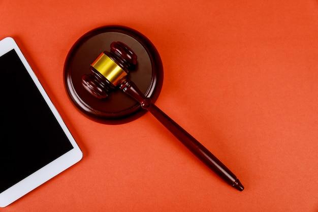 デジタルタブレットの空白の画面と裁判官の木製の小槌を持つ弁護士のためのワークスペース