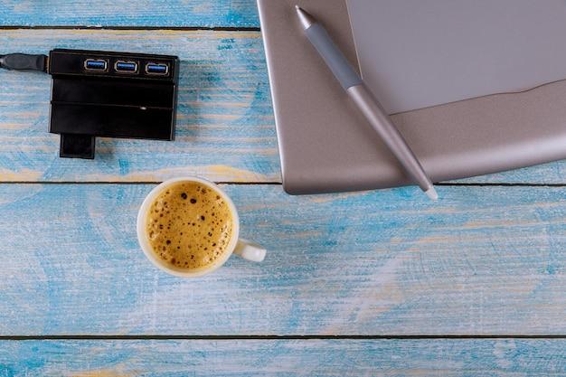 Дизайнер работает на ноутбуке в офисе на графическом планшете в офисе на чашке кофе эспрессо
