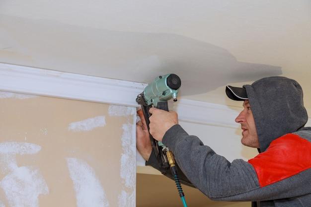 天井のモールディングをクラウンにエアネイルガンを使用する大工