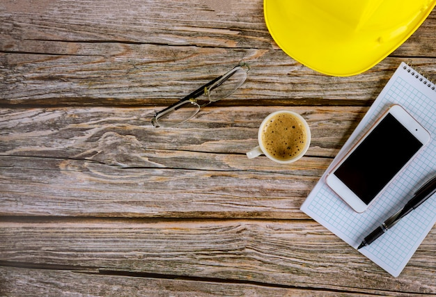 Рабочий стол строителей архитектор офисный стол, пустой открытый блокнот с ручкой на желтой каске с чашкой кофе, очки смартфон на деревянный стол