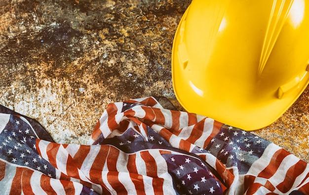 幸せな労働者の日米国愛国心が強い建設ヘルメットアメリカの国旗は木製デッキテーブルの上。