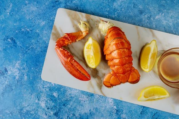 Ужин с вареными готовыми к употреблению кусочками омаров на столе с лимоном и соусом