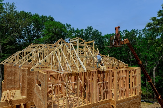 新しい家の屋根のブームトラックフォークリフトで持ち上げられている木製の屋根トラス