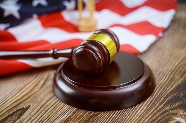 アメリカの弁護士は、アメリカの国旗の木製のテーブルに砂時計の裁判官の小槌を持つ米国の法的機関