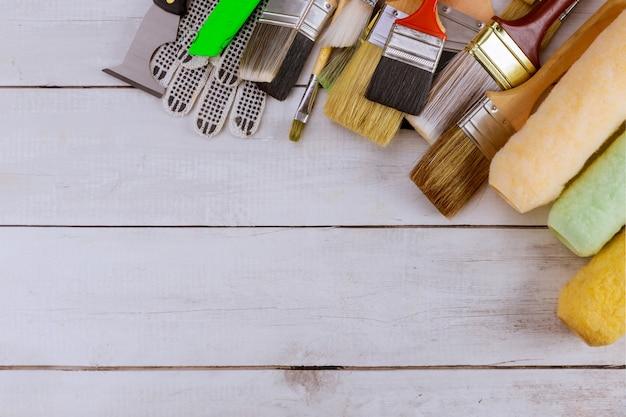 ペイントツールのさまざまなペイントブラシと木製のテーブル上のローラー