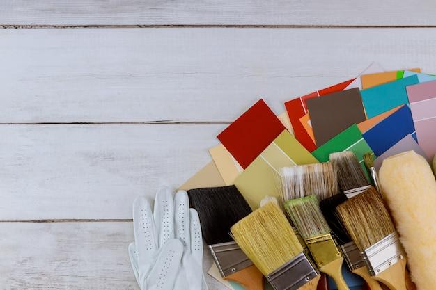 デコレーター作業テーブルの修理、改修塗装色選択パレットウッドの背景にさまざまなサイズのペイントブラシ