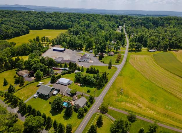 Вид с воздуха с высоты поселка с домами, улицами, полями, лугами летом