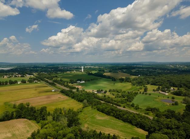 Красивый панорамный пейзаж красивой природой высоты зеленого поля против в лесу
