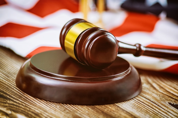 アメリカの弁護士は、アメリカの国旗の木製のテーブルに裁判官の小槌を持つアメリカの法律事務所