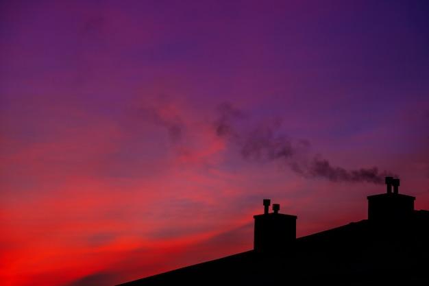 Вид с воздуха на пейзаж с крышами, восход солнца в первой половине дня. снежные домики с дымом