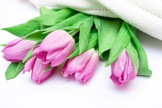 白いニットの背景にカットピンクのチューリップの花束をクローズアップ