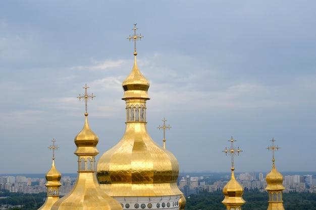 正統派キリスト教修道院。中世の大聖堂とキエフ・ペチェルシク大修道院の教会の黄金のドーム、雲と青い空。歴史的な文化の聖域。