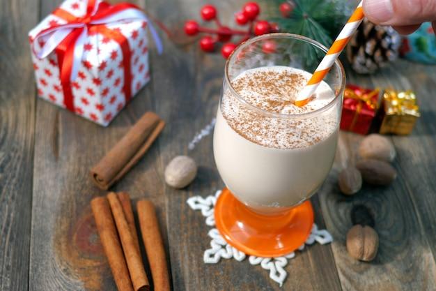 挽いたナツメグ、ガラスのシナモンと自家製の伝統的なクリスマスのスパイシーな飲み物のエッグノッグを準備します。