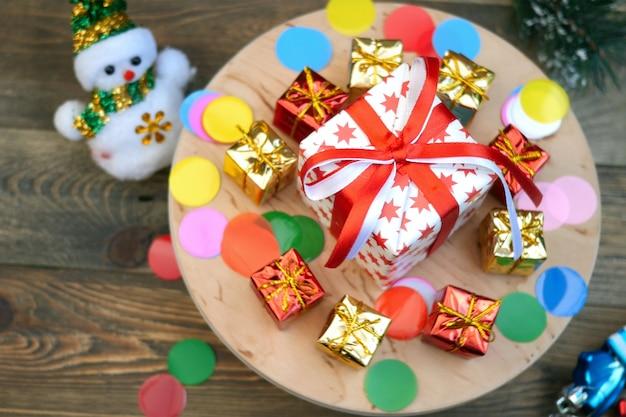 装飾的なクリスマスプレゼントボックスコレクションは、木製のスタンドに回転します。